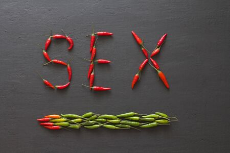 Word Sex Red Hot Chili Peppers On Black Background on Black Table. Swx letter arranged from red chili peppers. Copy space for your text. Flat lay, top view. Words from food and vegetables. Erotica.