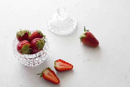 Beautiful red strawberry in glass round bowl. Strawberries on a light white concrete background. Rustic style. Cut strawberries, half. Horizontal. Top View, Copy Space For Your Text.