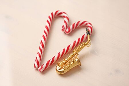 New Year's card - golden saxophone alto and candy cane. White background.