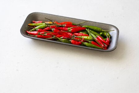 Red Hot Chili Peppers On White And Light Gray Modern Background or White Table. A Lot of Red Chilli Peppers. Green Hot Chili Peppers. Copy space for your text. Flat lay, top view.
