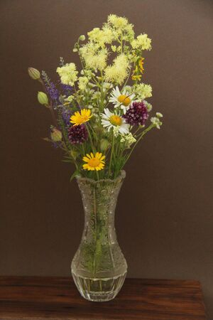 Summer wildflowers in a crystal vase. A beautiful summer bouquet on a dark background. Chamomile, wild onion, Veronica long-leaved. vertical, vertical design. Banque d'images