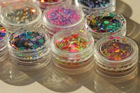 Multi colored Sequins for the design of nails in a Jar. Glitter in jars. Foil for nail service. Photo set. Sparkling beauty shimmer, glitter. Bright background of glitter. Top view. 写真素材