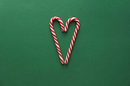Heart from Candy. Candy Canes Red-White in the Heart Form Lie on the Green Background, View From above. For your Decoration of Postcards, New Year and Christmas. Place for Text. Top view