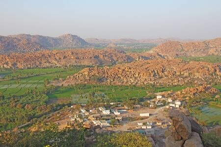 Green rice fields or terraces in the village of Hampi. Palm trees, sun,rice fields, large stones in Hampi. Tropical exotic landscape. Beautiful green valley. View from above. 写真素材
