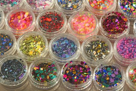 Multi colored Sequins for the design of nails in a Jar. Glitter in jars. Foil for nail service. Photo set. Sparkling beauty shimmer, glitter. Bright background of glitter. Top view.