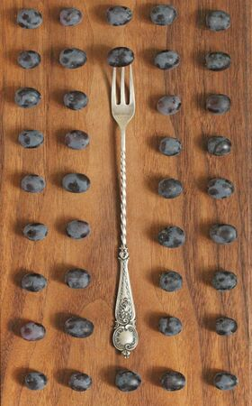 Grapes. Conceptual design. The grapes are arranged in rows around the vintage fork, on a wooden background. Unusual design. 写真素材
