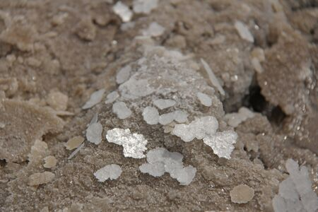 Pieces of salt lie on the sand. Macro. Lake Baskunchak, Russia.