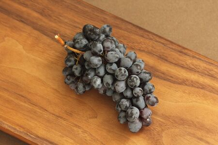 Grapes. A bunch of dark, black grapes lies on a wooden board.
