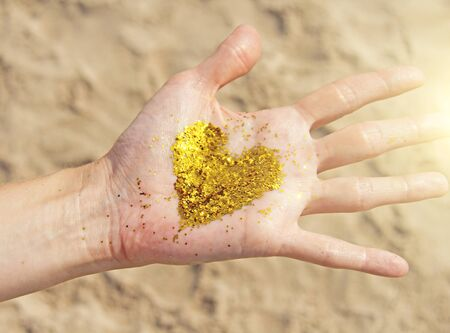 A golden shining heart lies in the hands of the girl. Golden heart. Heart on a background of sand. 写真素材