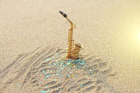 The golden alto saxophone stands on the sand against the background of blue shimmers. Romantic musical background. Musical cover, creative. Design with copy space.