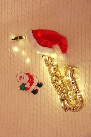 New Years card - golden saxophone alto, garland, Santa Claus, red cap.