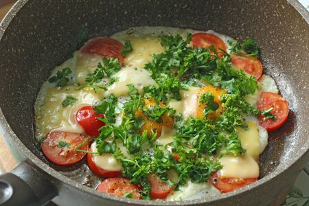 Fresh fried eggs are cooked in a frying pan, with tomatoes, cheese and greens. Vegetarian dishes. Bright healthy food. 写真素材