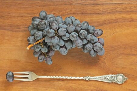 Grapes. A bunch of dark, black grapes lies on a wooden board close-up and a vintage fork.