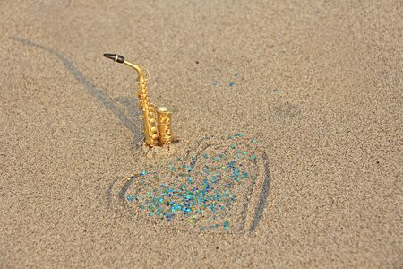 The golden alto saxophone stands on the sand next to the heart of sand and blue shining. Romantic musical background. Musical cover, creative. Design with copy space. 写真素材