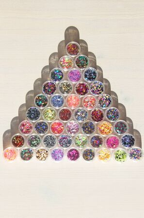 Multi colored Sequins for the design of nails in a Jar. Glitter in jars. Foil for nail service. Photo set. Sparkling beauty shimmer, glitter. Bright background of glitter a triangle. Top view