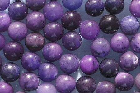 Natural Lilac and violet mineral stones beads. Lilac and violet natural background made of round stone beads.