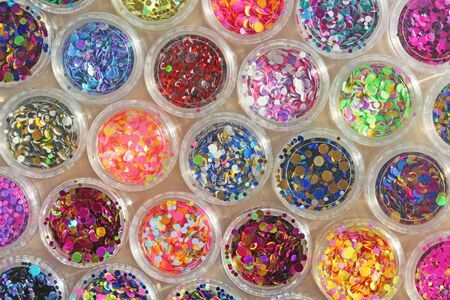 Multi colored Sequins for the design of nails in a Jar. Glitter in jars. Foil for nail service. Photo set. Sparkling beauty shimmer, glitter. Bright background of glitter. Top view. Imagens