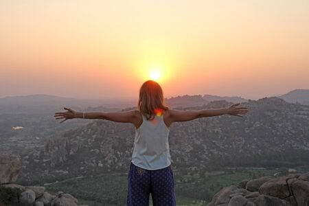 The girl at sunset. The girl stands with her back on the top of the mountain and looks at the sunset,  She spread her arms out to Hampi. Meditation, alone with nature, silence. Hands up.