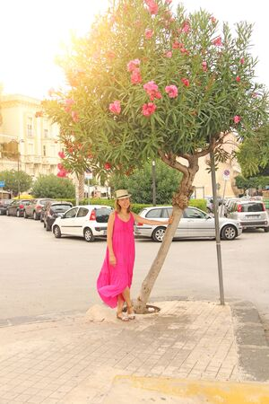 Young Romantic Girl on the Street in Italy in Pink Long Bright Dress and Slap. The island of Sicily, Italy. Zdjęcie Seryjne