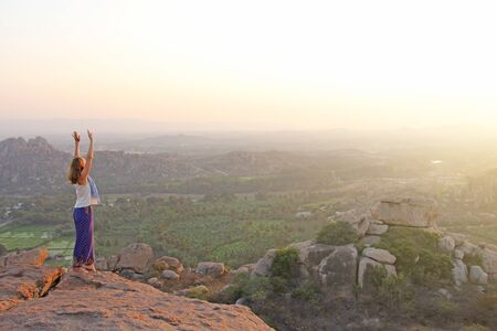 The girl stands on top of the mountain and looks at the sunset at Hampi and welcomes the sun with her hands up. Meditation, harmony, alone with nature, silence. Large stones and rice fields in Hampi. Zdjęcie Seryjne