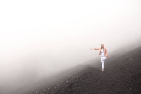 The girl on Mount Etna. The Etna volcano crater. Black Volcanic Earth, Volcanic Lava and Stones.  Dense Fog on Mount Etna. Place for Text. The island of Sicily, Italy.