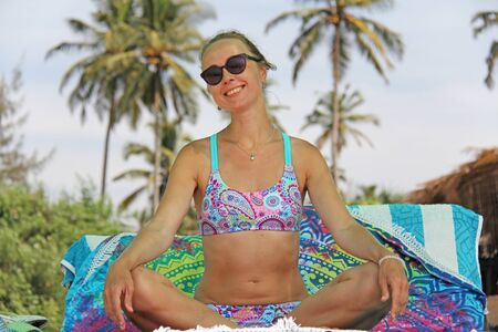 A young and beautiful girl, wearing sunglasses, in a beautiful separate swimsuit, sits in a lotus position and sunbaths on the beach under a canopy, against the backdrop of palms and blue skies.