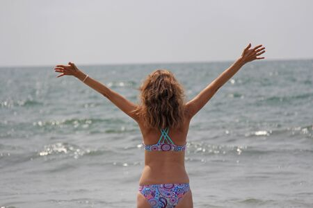 A young and beautiful girl, wearing sunglasses, in a beautiful separate swimsuit and blond hair, stands and smiles against the background of the sea. A girl looks at the sea with open hands.