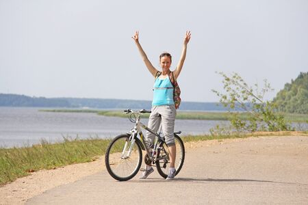 A girl is riding a bicycle in the summer.