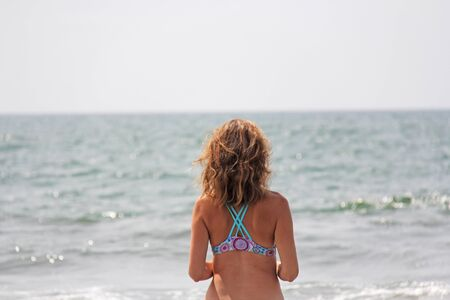 A young and beautiful girl, wearing sunglasses, in a beautiful separate swimsuit and blond hair, stands and smiles against the background of the sea. The girl is looking at the sea. Zdjęcie Seryjne