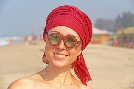Beautiful girl freak with a red armband on her head, on the background of the sea. Summer girl in round wooden glasses. Unusual glasses.
