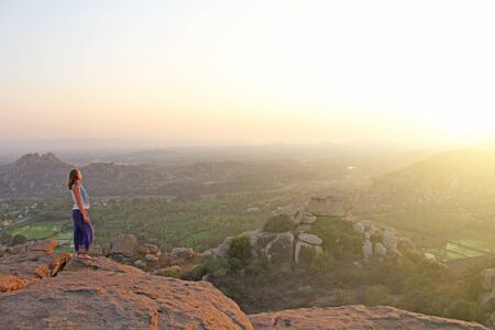 A girl is watching the sunset in Hampi. The girl stands on top of the mountain and looks into the distance. Meditation, harmony, alone with nature, silence. Large stones and rice fields in Hampi. Zdjęcie Seryjne