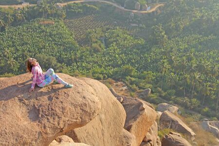 A young girl on a background of sunrise or sunset sits on top of a mountain or on a large rock. Alone with nature. Meditation in nature in Hampi. Vijayanagar, karnataka, unesco.