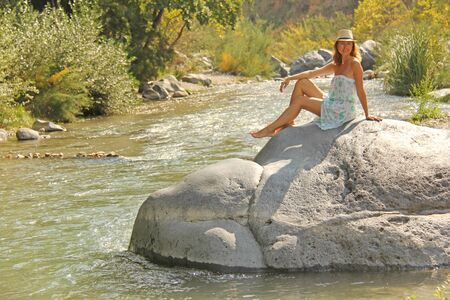 A Young Girl Sits On A Stone In A Dress And A Hat On The Bank Of A Mountain River. Autumn leaves.