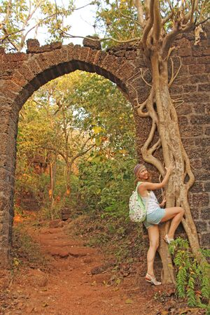 Red Fort in India, Goa. Roots and trunks of old trees captured the old walls of the ancient fort. Girl on the background of Red Fort.