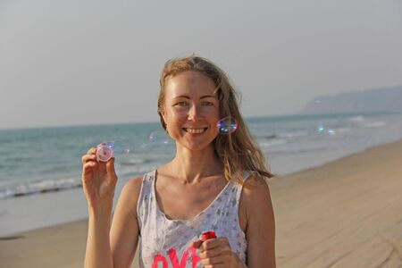 A young girl with blond hair smiles and launches soap bubbles on the background of the sea. Fun, entertainment and relaxation at sea.