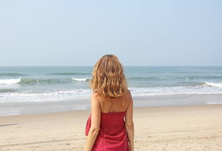 A beautiful girl with blond hair, in a red dress looks at the sea and stands with her back. Summer girl on the sea. Tenderness, alone with nature, pacification. Zdjęcie Seryjne