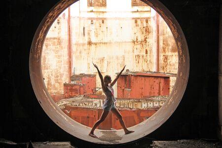 Centrale nucleare abbandonata. Russia, Crimea, Shelkino. Costruzione abbandonata, sfondi di ferro. Cerchio di ferro e la ragazza dentro. Archivio Fotografico