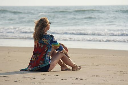 Young and beautiful girl in sunglasses, with blond hair, sits on the sand and looks at the sea. A girl in a bright summer dress is resting on the beach.