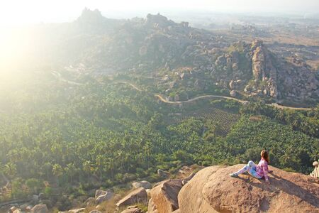 A young girl on a background of sunrise or sunset sits on top of a mountain or on a large rock. Alone with nature. Meditation in nature in Hampi. Vijayanagar, karnataka. Zdjęcie Seryjne