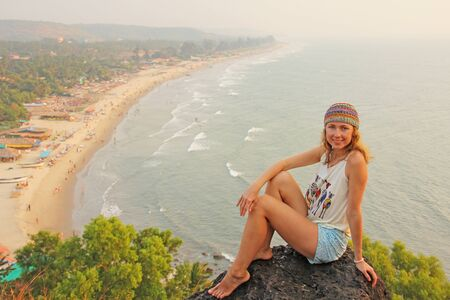 Young and beautiful girl wearing a hippie cap sits on top of a mountain and smiling, on a background of Goa beach, Arambol, India. Beach village Arambol.