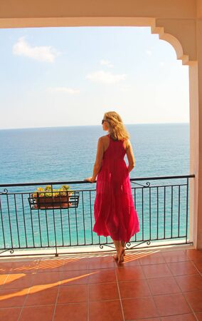 A Young Girl in a Long Pink Dress Costs and Looks at the Sea. The island of Sicily, Italy.