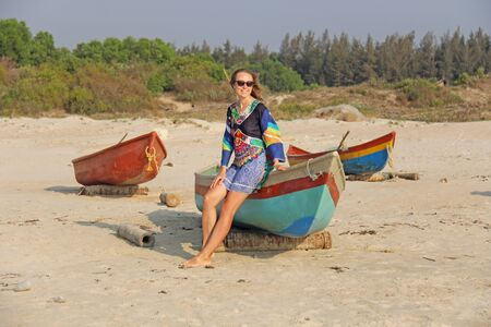 Young and beautiful girl in sunglasses, with blond hair, sitting on a boat, smiling on the beach and looking at the sea. A girl in a bright summer dress. Indian boats.