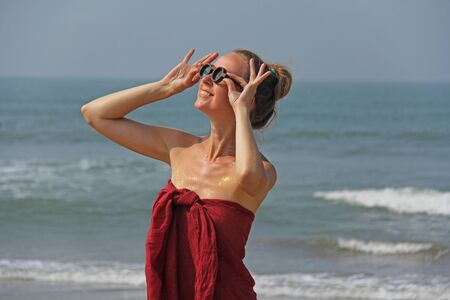 Beautiful girl freak in a red dress and blond hair, on the background of the sea. Summer girl in round wooden glasses, smiling. Unusual glasses. Zdjęcie Seryjne - 133475536
