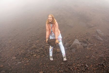 The girl on Mount Etna. The Etna volcano crater. Black Volcanic Earth, Volcanic Lava and Stones.  Dense Fog on Mount Etna. Place for Text. The island of Sicily, Italy. Zdjęcie Seryjne - 133475550