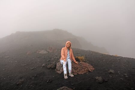 The girl on Mount Etna. The Etna volcano crater. Black Volcanic Earth, Volcanic Lava and Stones.  Dense Fog on Mount Etna. Place for Text. The island of Sicily, Italy. Zdjęcie Seryjne - 133475552