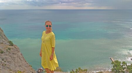 A young girl in a yellow dress stands against the azure sea. Beautiful seascape, rest, tourism, travel.