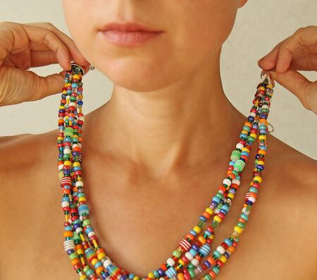 Bright beads of Murano glass on a young girl. A girl dresses and button beads, jewelry. Zdjęcie Seryjne