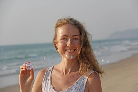 A young girl with blond hair smiles and launches soap bubbles on the background of the sea. Fun, entertainment and relaxation at sea. Zdjęcie Seryjne - 133475560