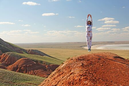 Beautiful mountains of red clay against the blue sky. Landscape of the desert. Space for text. dramatic landscape of the clay desert. A girl is jumping atop a mountain. Zdjęcie Seryjne