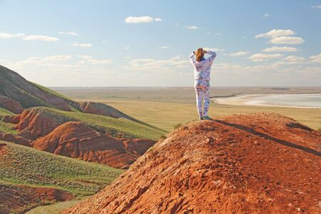 Beautiful mountains of red clay against the blue sky. Landscape of the desert. Space for text. dramatic landscape of the clay desert. The girl is standing at the top of the mountain.